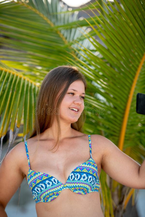 Young woman with smartphone in front of the palm. Happy young woman wearing bikini taking selfie using smartphone in the summer day between palm on the beach in stock photography