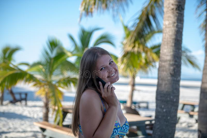 Young woman with smartphone in front of the palm. Young woman wearing bikini speaking on cell phone on the background of palm trees stock image