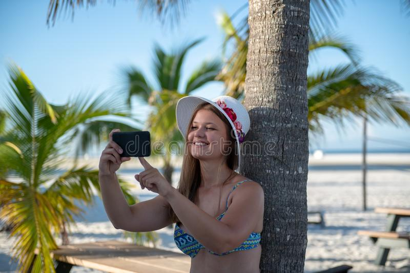 Young woman with smartphone in front of the palm. Young woman wearing bikini using smartphone on the background of palm trees royalty free stock photos