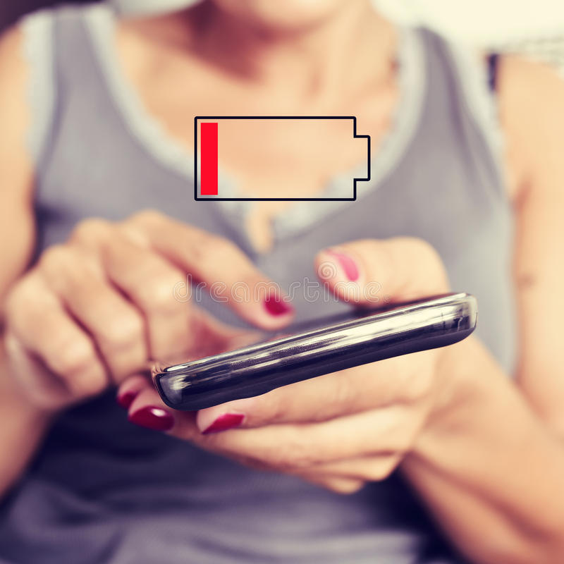 Young woman with a smartphone with low battery stock photography