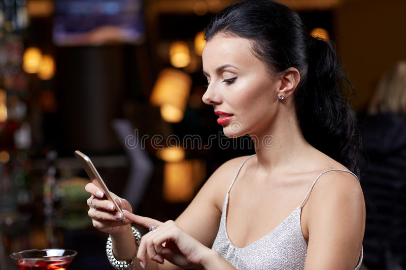 Young woman with smartphone at night club or bar royalty free stock images