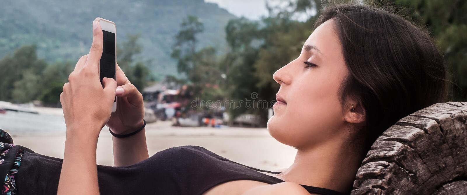 Young woman with smartphone relaxing on tropical beach. Young woman reading sms, texting on smartphone and relaxing on tropical beach royalty free stock image