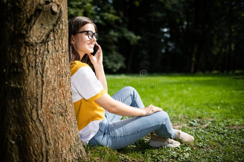Young Woman With Smartphone Resting Against a Tree royalty free stock photography