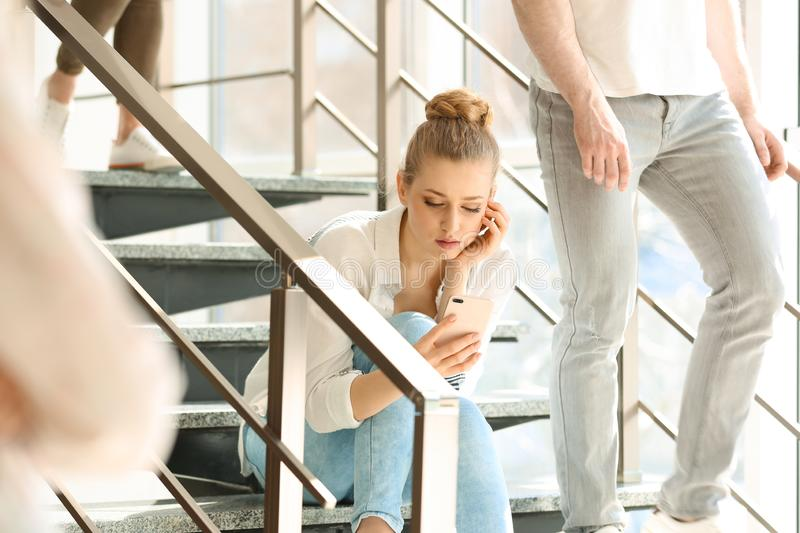 Young woman with smartphone sitting. Alone among people stock photos