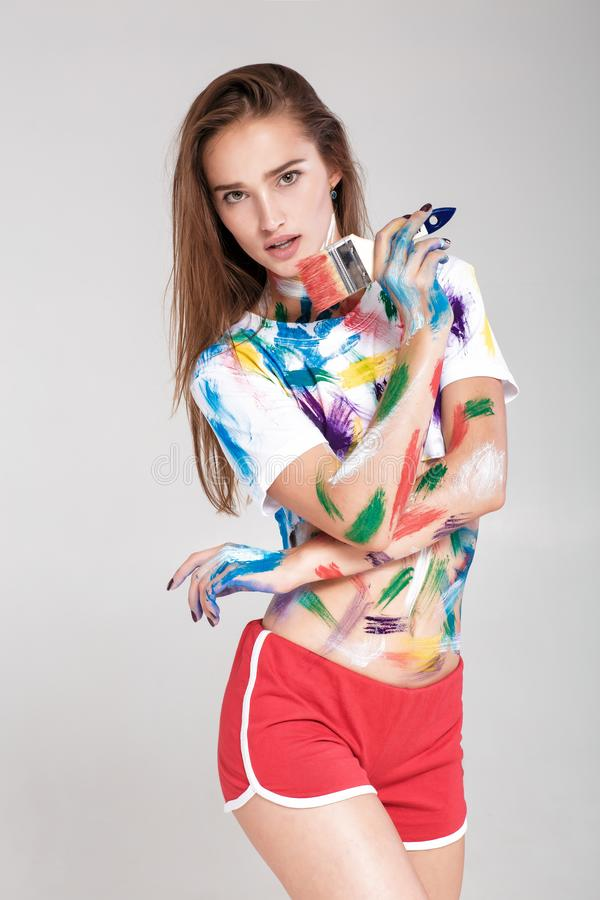 Young woman smeared in multicolored paint. royalty free stock photos