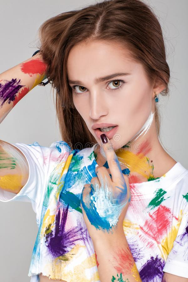 Young woman smeared in multicolored paint. stock photo