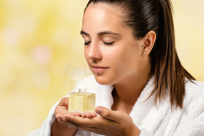 Young woman smelling essential oil fragrance. Close up portrait of woman in white spa gown smelling essential oil fragrance.Girl holding little bottle with stock photo
