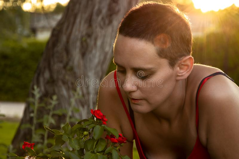 Young woman smelling red flowers stock image