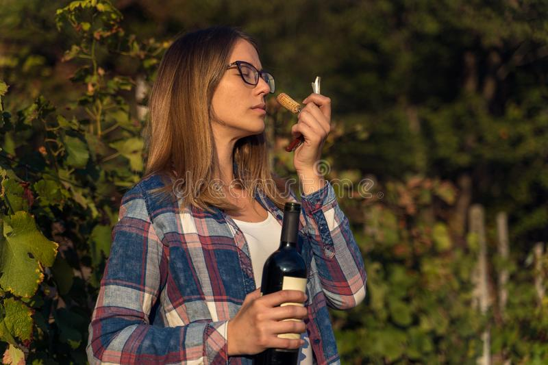 Young woman smelling red wine cork. tasting wine stock image