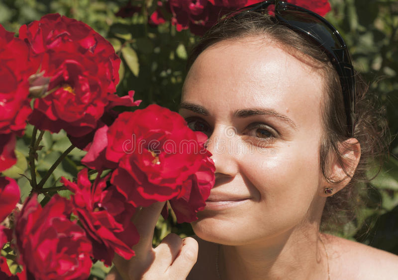 Young woman smelling roses royalty free stock images