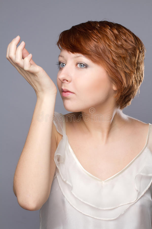Young woman smells pafrume on her hand. Portrait of beautiful woman she smells pafrume on her hand royalty free stock photography