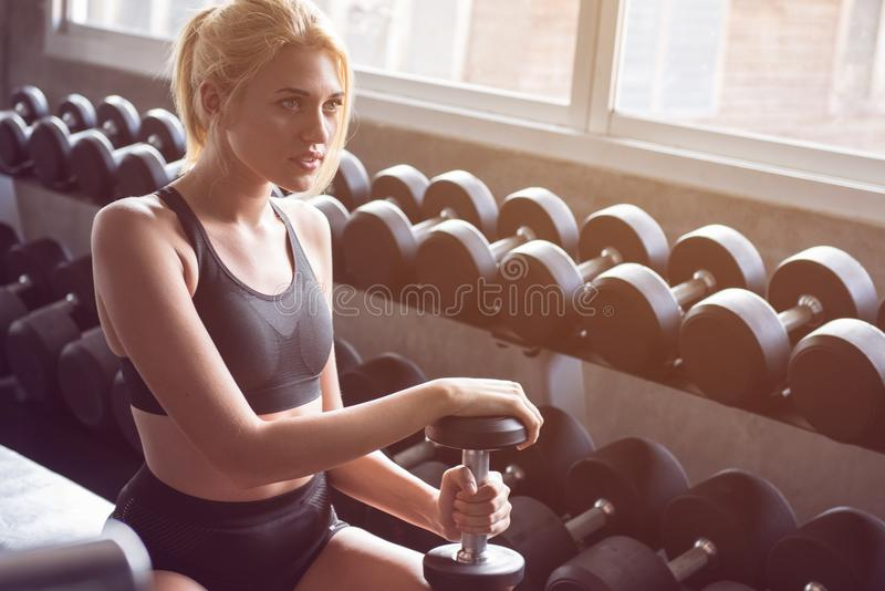 A young woman smile and training with dumbbell stock image