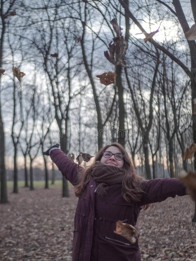 Young woman smiles in the middle of the forest while the leaves fall on her stock image