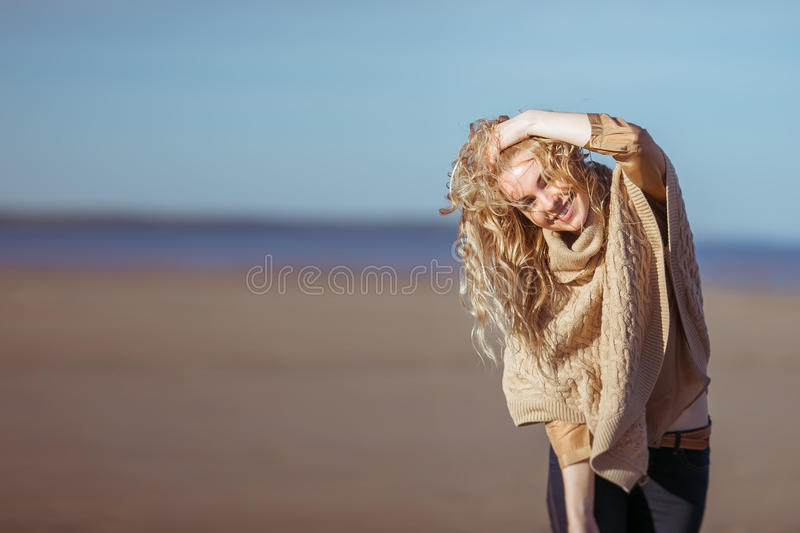 A young woman is smilin holding her hand in her hair stock photos