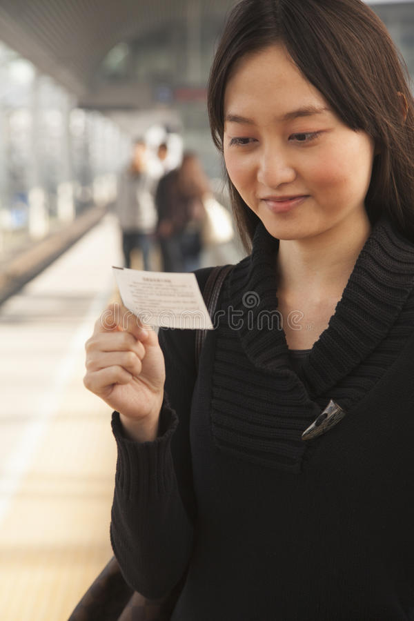 Free Young Woman Smiling And Looking At Train Ticket On Railroad Platform Royalty Free Stock Images - 31130039
