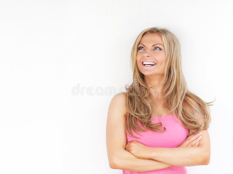 Young woman smiling with arms crossed and looking up. Portrait of a beautiful young woman smiling with arms crossed and looking up against white background royalty free stock photos