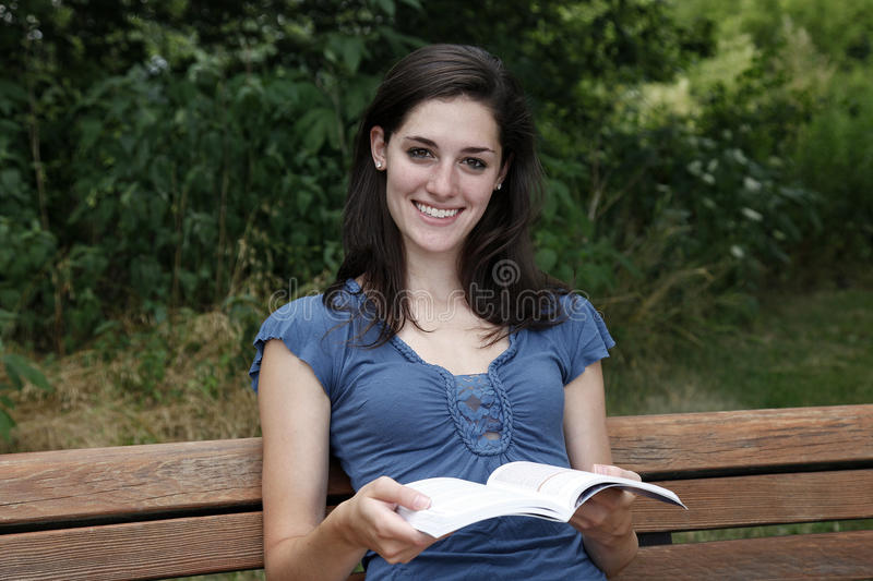 Download Young Woman Smiling With Book In Her Hand Stock Image - Image: 15331783