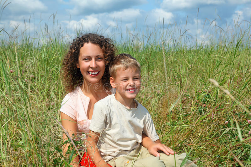 Young woman and smiling boy sitting on meadow stock images