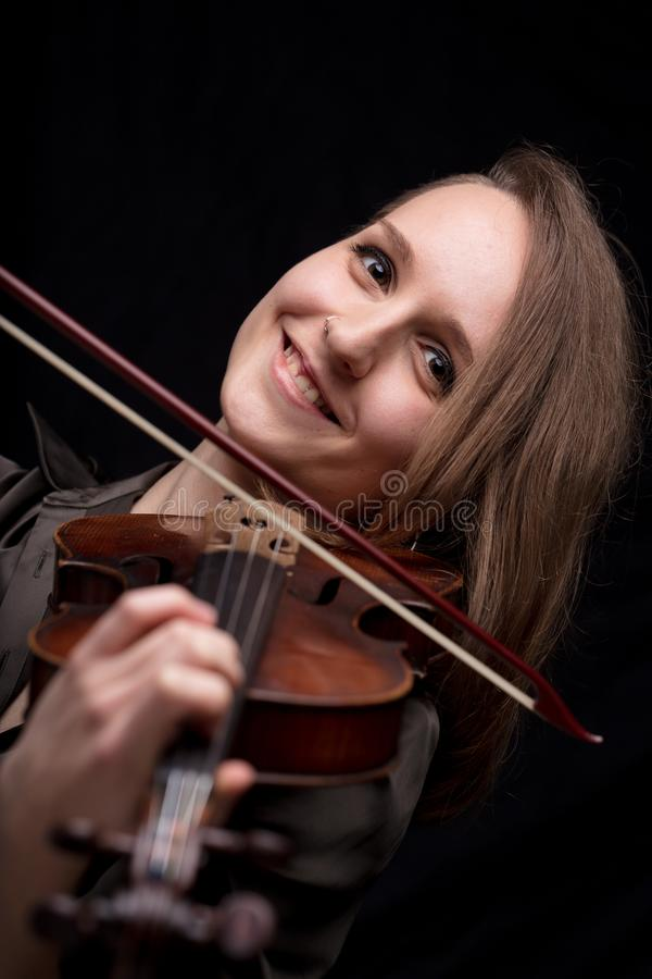 Happy woman playing baroque violin. Young woman smiling and cheering while playing a baroque violin on a black background stock image