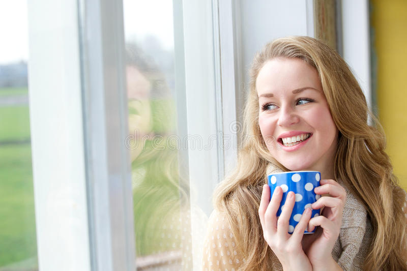 Young woman smiling with cup of tea royalty free stock photo