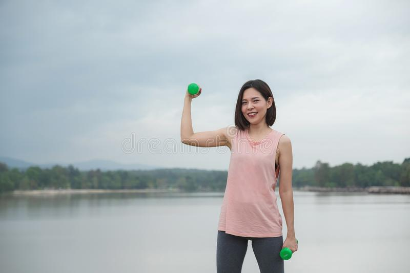 Young Woman Smiling exercising with dumbbell at the park. Healthy Lifestyle concept royalty free stock photo