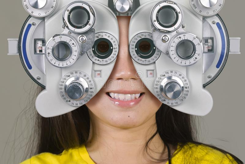 Young woman smiling happy looking through optometric hospital device and checking eyes having sight exam in ophthalmology health royalty free stock photography
