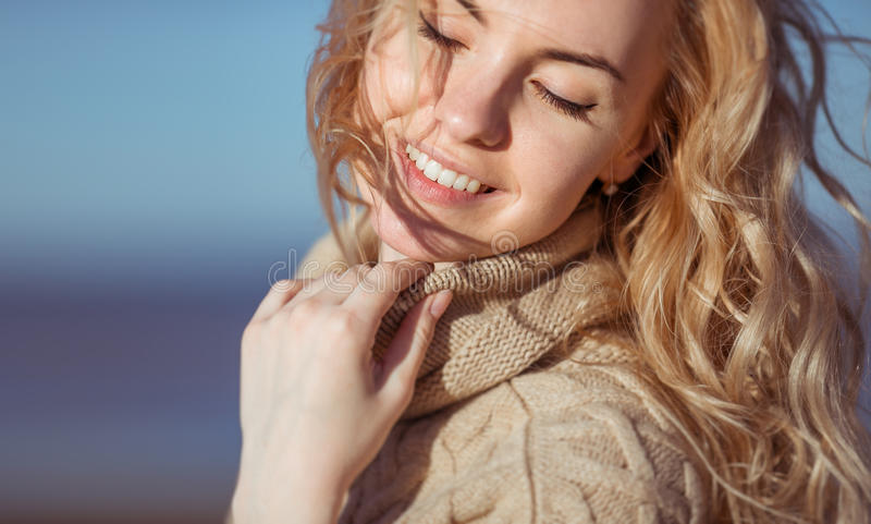 A young woman is smiling holding her hand on her collar stock photos