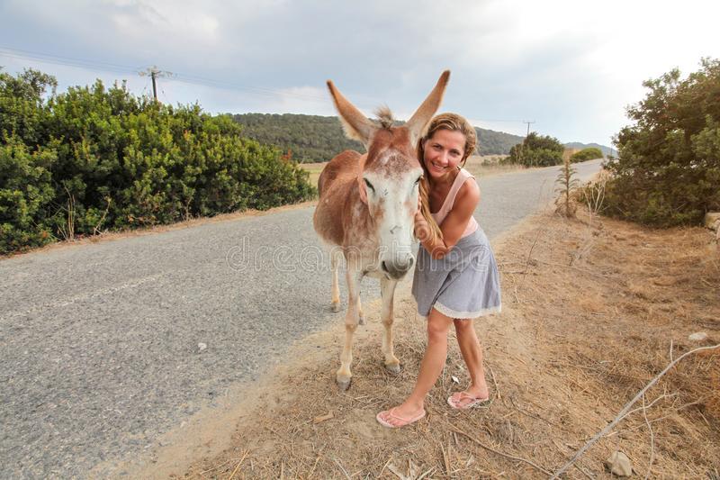 Young woman smiling, posing  with wild donkey, giving him hug. These animals roam freely in Karpass region of Northern Cyprus royalty free stock photo