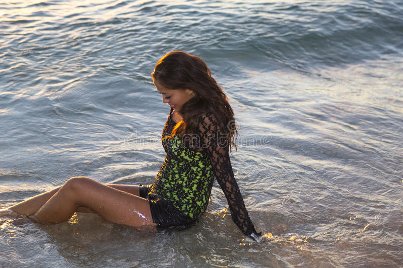 Young Woman Smiling While Sitting In The Ocean Stock Photo