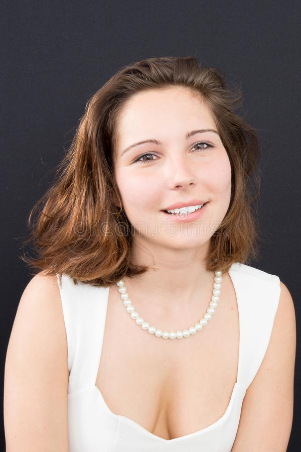 young woman smiling in white dress stock photo