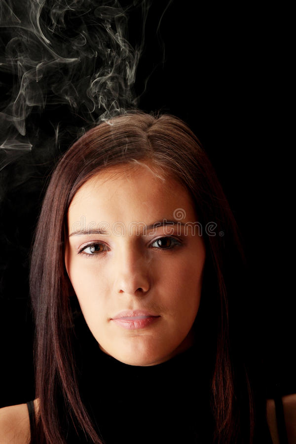 Young woman smoking. Over black background royalty free stock photography