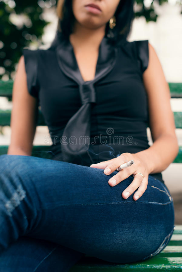 Download Young Woman Smoking Cigarette On Bench Stock Image - Image: 26301317