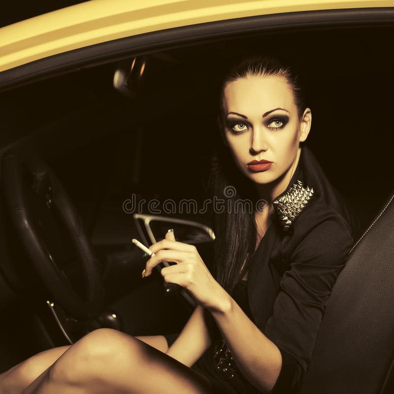 Young fashion woman smoking cigarette in a car. Young woman smoking cigarette in a car Stylish fashion model with bun up do hair style in night outdoor stock photography