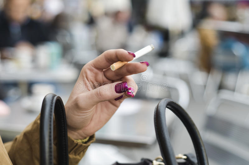 Young woman smoking a cigarette. Closeup of a young caucasian woman, with purple nail polish in her fingernails, smoking a cigarette sitting at a table in the stock photography