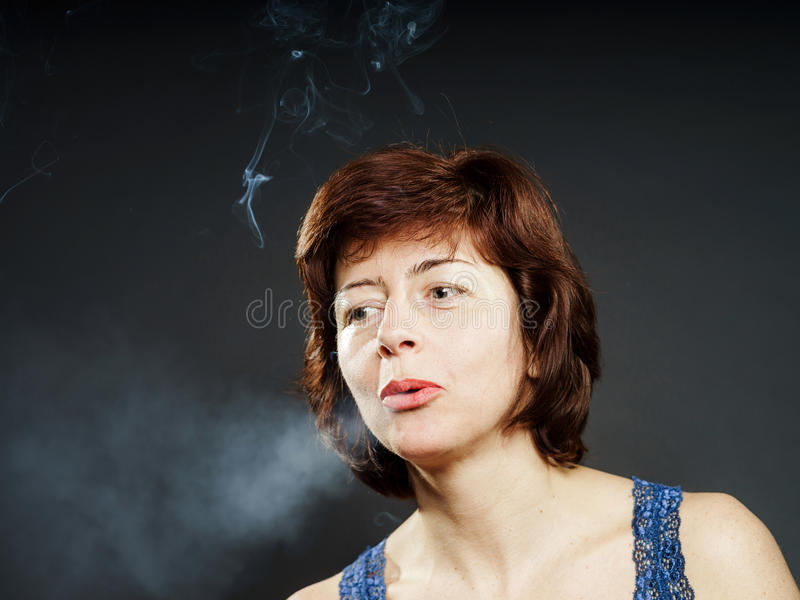 Young woman smoking cigarette, healthcare concept. Isolated stock image