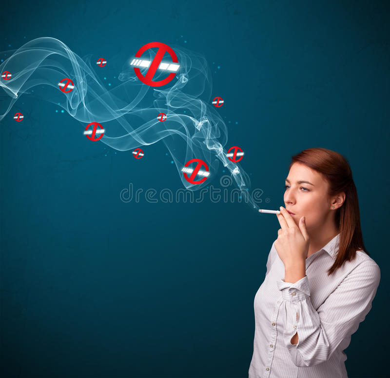 Young woman smoking dangerous cigarette with no smoking signs. Beautiful young woman smoking dangerous cigarette with no smoking signs royalty free stock photos