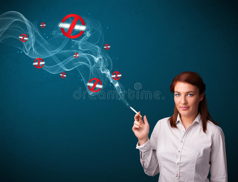 Young woman smoking dangerous cigarette with no smoking signs. Beautiful young woman smoking dangerous cigarette with no smoking signs stock images