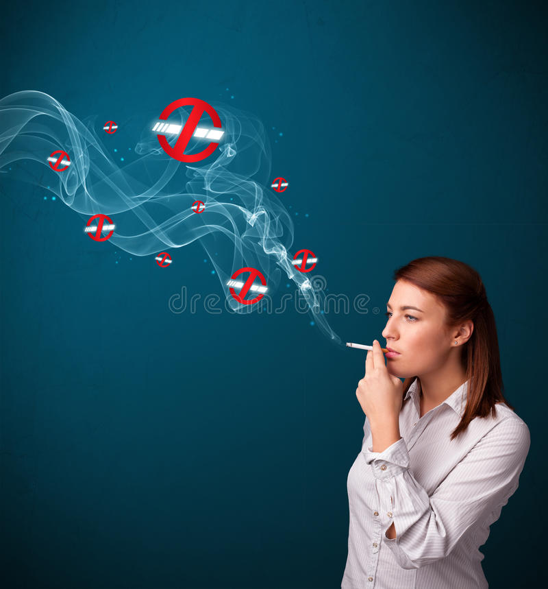 Young woman smoking dangerous cigarette with no smoking signs. Beautiful young woman smoking dangerous cigarette with no smoking signs stock image