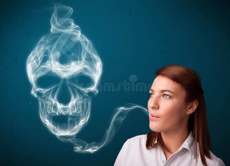 Young woman smoking dangerous cigarette with toxic skull smoke. Pretty young woman smoking dangerous cigarette with toxic skull smoke royalty free stock image