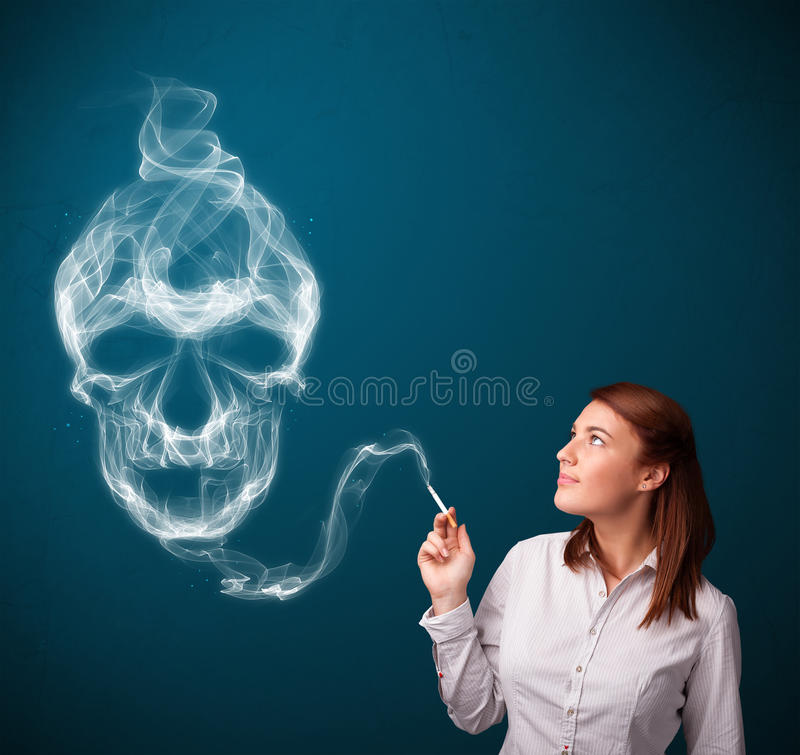 Young woman smoking dangerous cigarette with toxic skull smoke. Pretty young woman smoking dangerous cigarette with toxic skull smoke royalty free stock photography