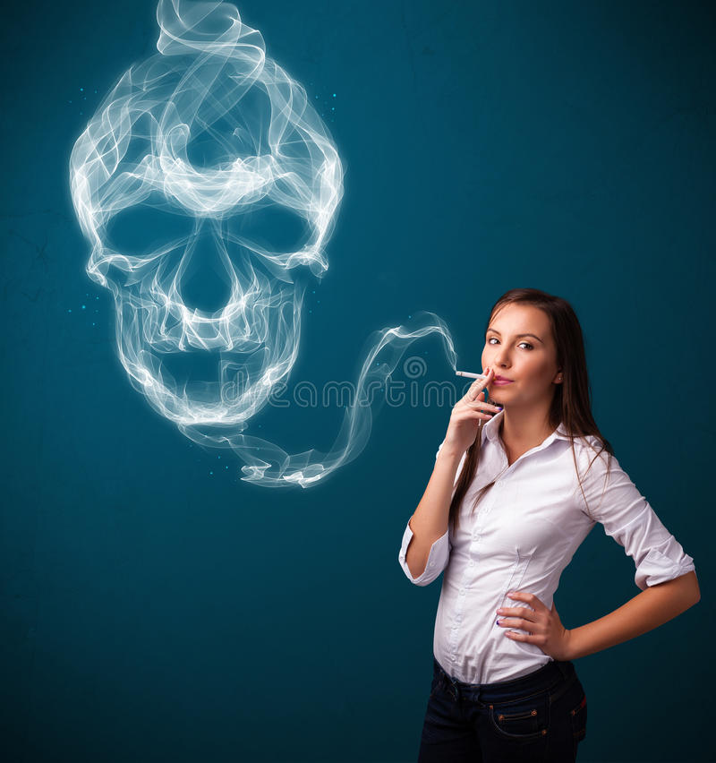Young woman smoking dangerous cigarette with toxic skull smoke. Pretty young woman smoking dangerous cigarette with toxic skull smoke stock images