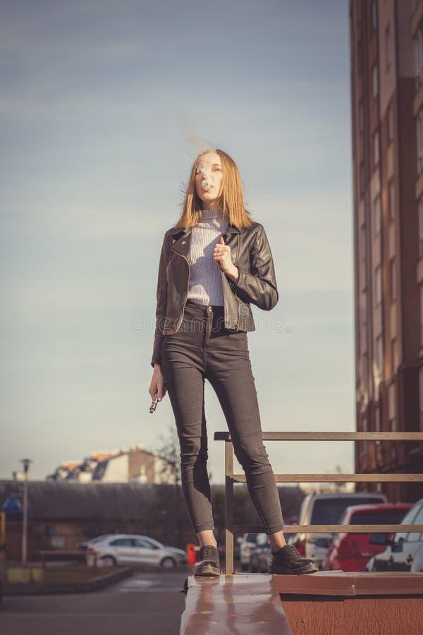 Smoking electronic cigarette. Young woman smoking electronic cigarette in the city stock photos