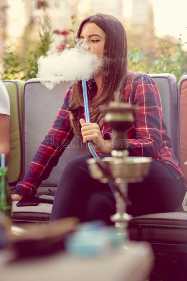 Young woman smoking a hookah outdoors. The pleasure of smoking. City in background royalty free stock photography