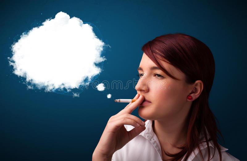 Young woman smoking unhealthy cigarette with dense smoke. Pretty young woman smoking unhealthy cigarette with dense smoke stock photography