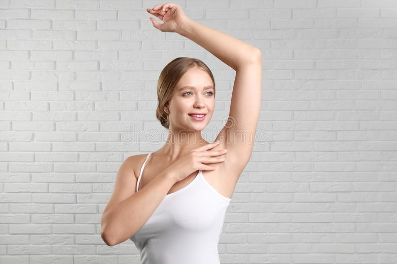 Young woman with smooth clean armpit  brick wall. Using deodorant royalty free stock images