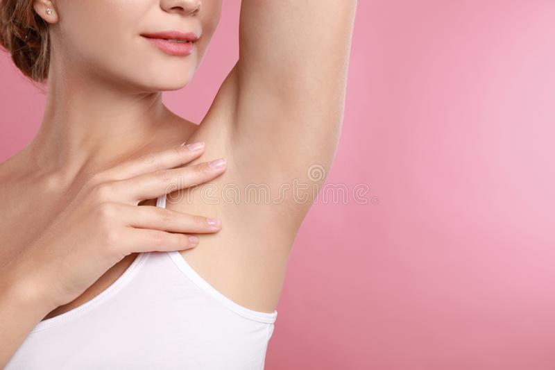 Young woman with smooth clean armpit on pink background. Using deodorant stock images