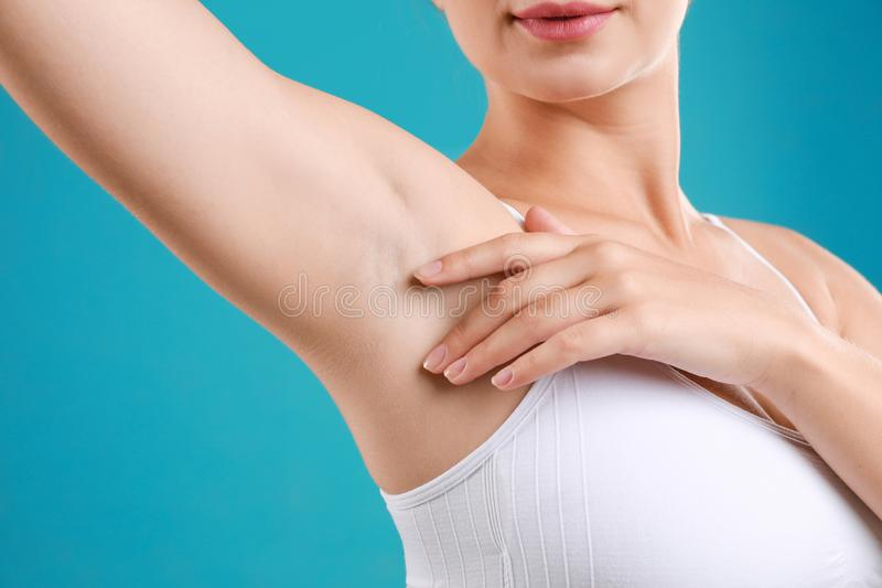 Young woman with smooth clean armpit on background, closeup. Using deodorant royalty free stock photography