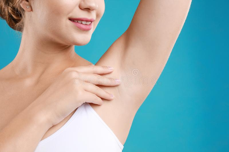 Young woman with smooth clean armpit on teal background. Using deodorant stock images