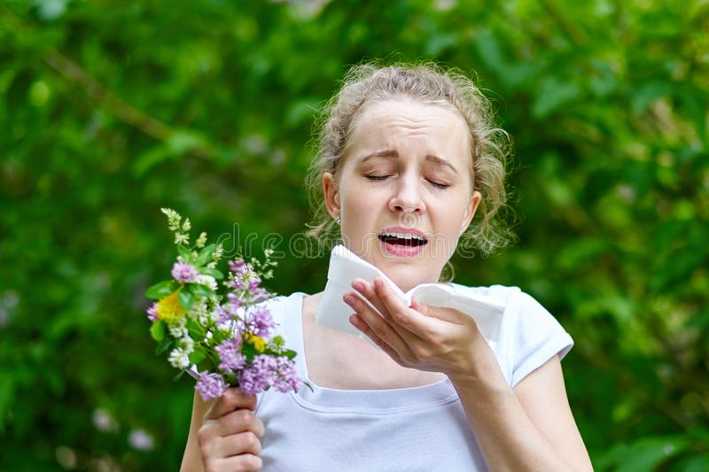 Young woman sneezing with bouquet of flowers. Concept: seasonal allergy royalty free stock image