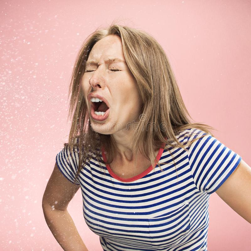 Young woman sneezing, studio portrait stock photo